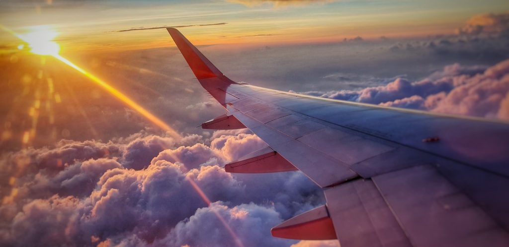 plane wing flying through clouds, sky and sunset